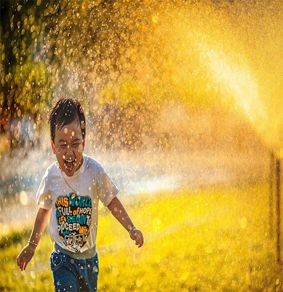 Φωτογραφία με παιδάκι που παίζει με τα νερά.