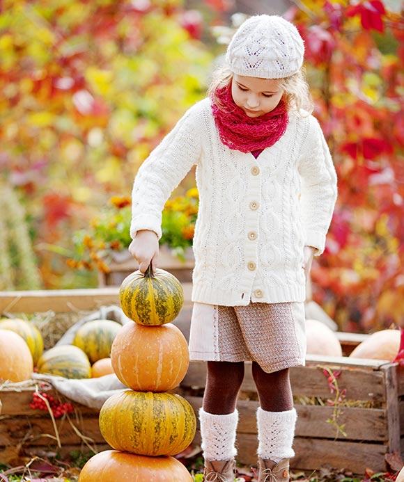κοριτσάκι με κολοκύθες σε φθινοπωρινό τοπίο